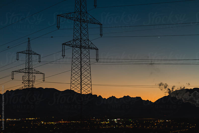 Electricity pylon and industrial cityscape at night by Leander Nardin for Stocksy United