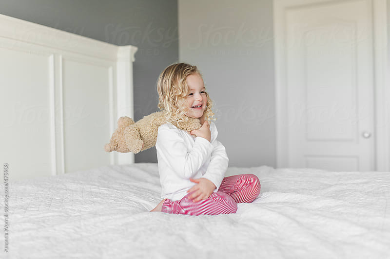 Happy young girl wearing red and white striped pajamas with teddy bear on shoulders by Amanda Worrall for Stocksy United