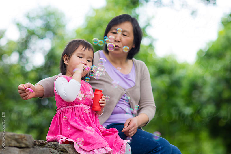 lovely little asian girl having good time with her gradmother outdoor by Bo Bo for Stocksy United