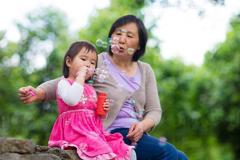 lovely little asian girl having good time with her gradmother outdoor by Bo Bo for Stocksy United