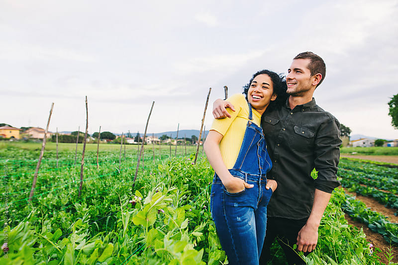 Portrait of couple standing in their orchard. by BONNINSTUDIO for Stocksy United