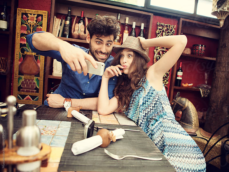 Silly couple in a restaurant. by Mosuno for Stocksy United