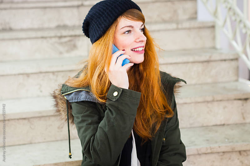 Trendy readhead woman having a phonecall. by Audrey Shtecinjo for Stocksy United