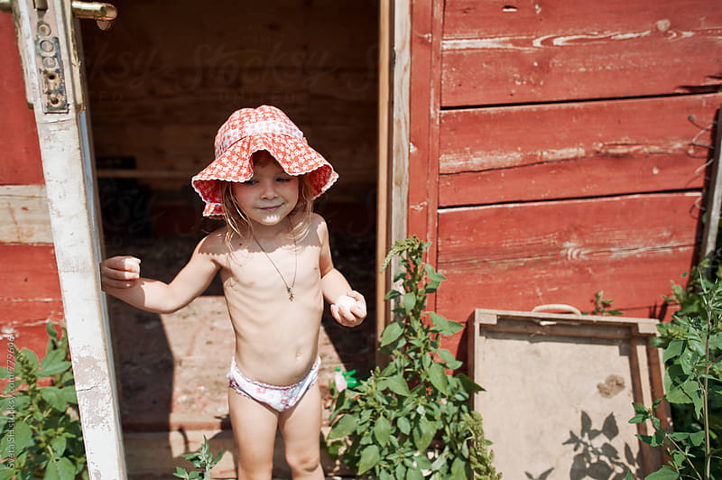Little girl in red panama  by Sveta SH for Stocksy United
