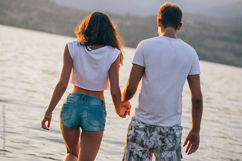 Couple holding hands and walking in the lake by michela ravasio for Stocksy United