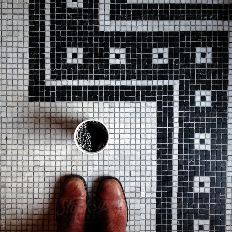 Overhead view of cafe culture wearing boots with coffee, straight up on a fancy tile floor by Holly Clark for Stocksy United