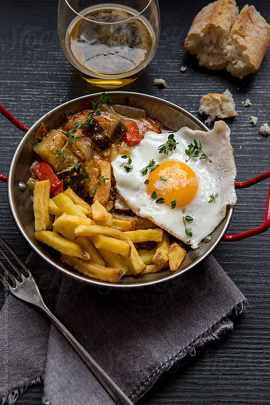 Ratatouille with fried egg and chips by Marta Muñoz-Calero Calderon for Stocksy United