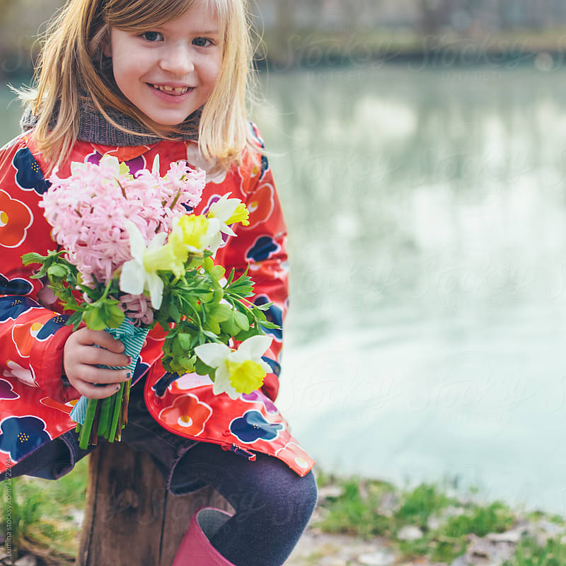 Smiling Girl Holding Flowers by Lumina for Stocksy United