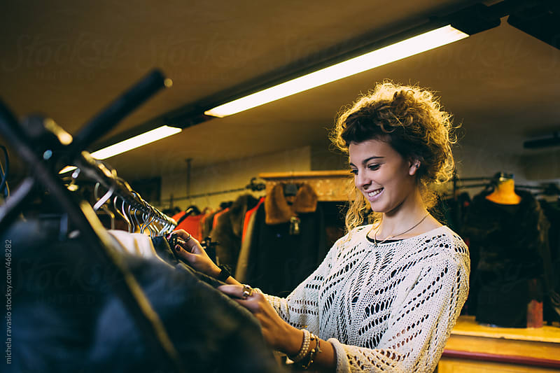Smiling woman browsing the racks by michela ravasio for Stocksy United