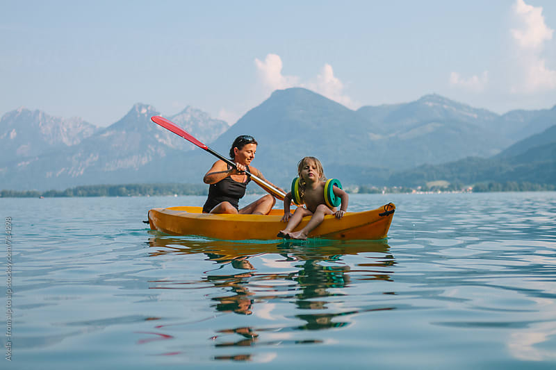 mother and son paddling in a canoe on a lake with mountains in the back by Leander Nardin for Stocksy United