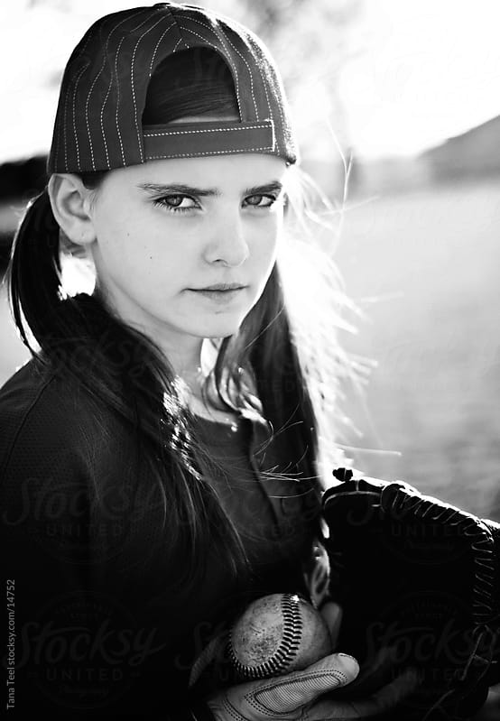 Young girl in baseball jersey with mitt and ball.  by Tana Teel for Stocksy United