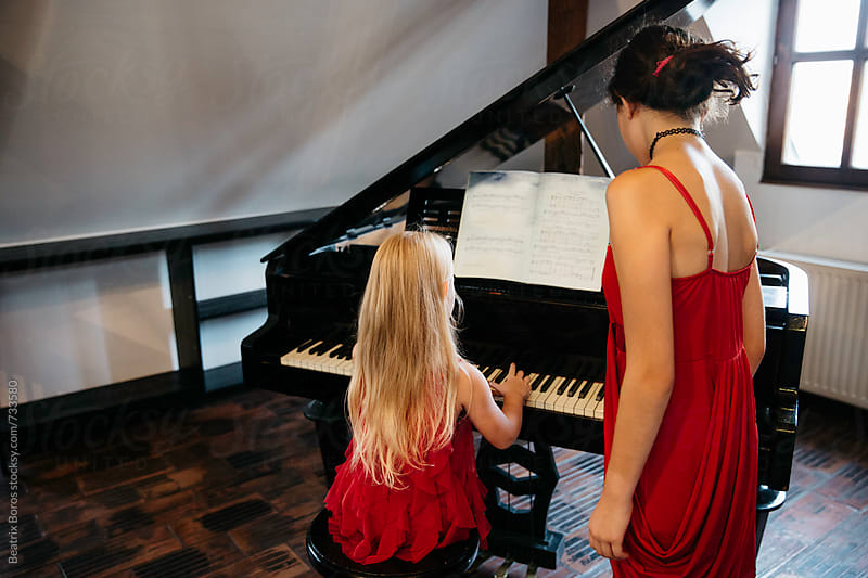 Little girl from behind playing the piano in the presence of her big sis by Beatrix Boros for Stocksy United