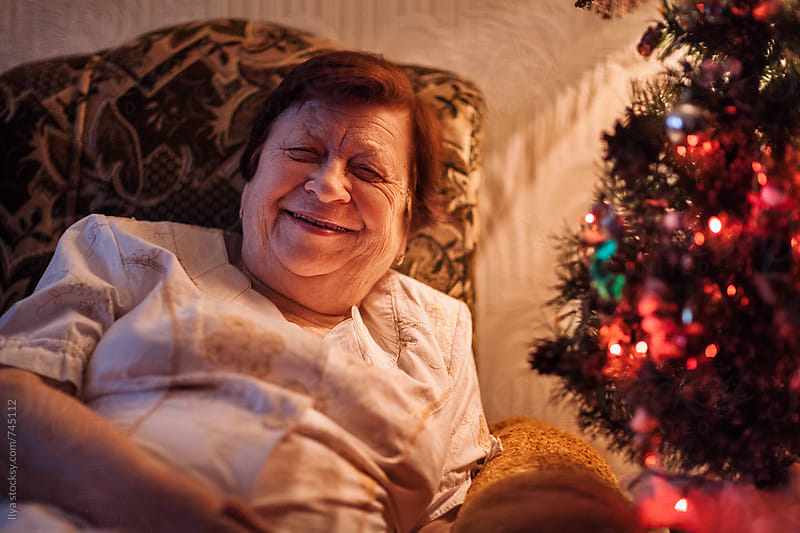 Portrait of old woman smiling looking at camera near Christmas tree by Ilya for Stocksy United