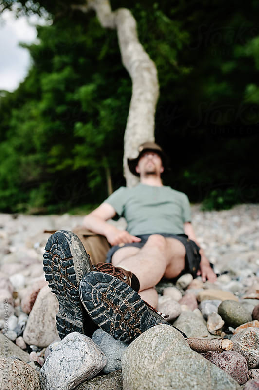 Man Relaxing, Leaning against a Tree Trunk by Claudia Lommel for Stocksy United