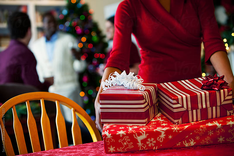 Christmas: Woman Setting Down Stack of Christmas Gifts by Sean Locke for Stocksy United