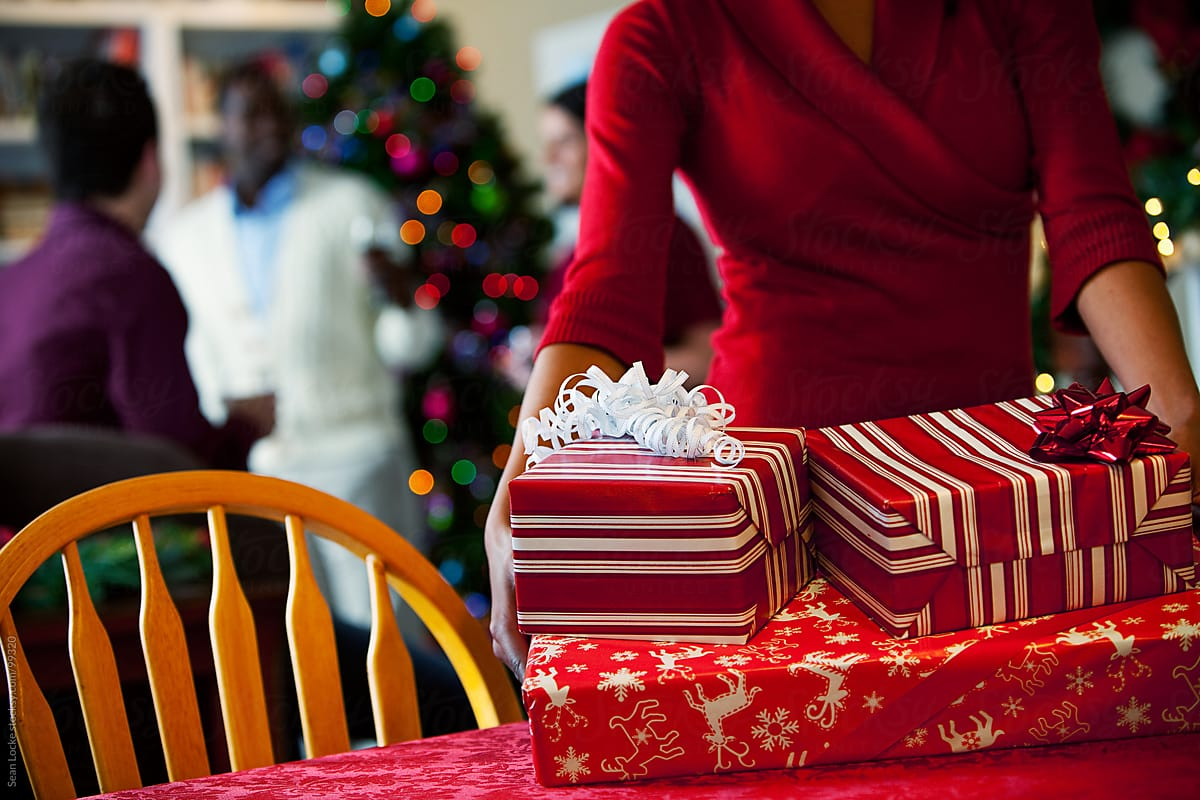 Christmas: Woman Setting Down Stack Of Christmas Gifts | Stocksy United