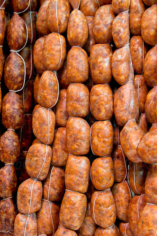 Chorizos hanging at the market by Bisual Studio for Stocksy United