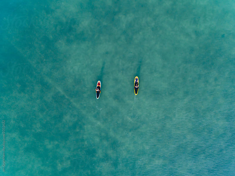 Aerial drone image of two women stand up paddleboarding in the o by Jen Grantham for Stocksy United