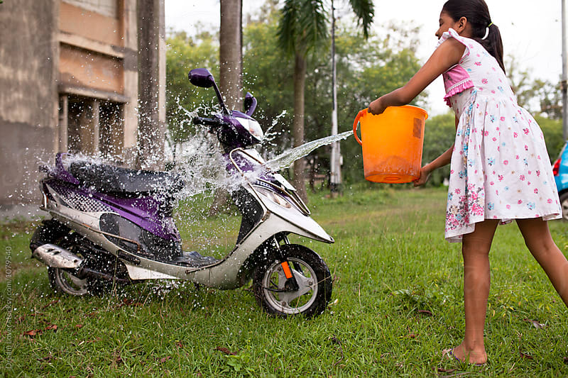 Teenage girl wadshing a two wheeler by PARTHA PAL for Stocksy United