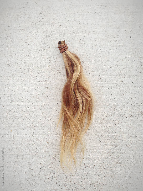 Cut ponytail of hair lying the ground by Nicole Mlakar for Stocksy United