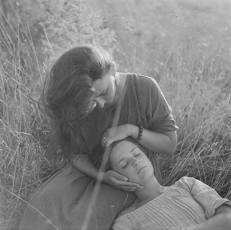 A black and white film portrait two young beautiful women lying on the grass by Anna Malgina for Stocksy United