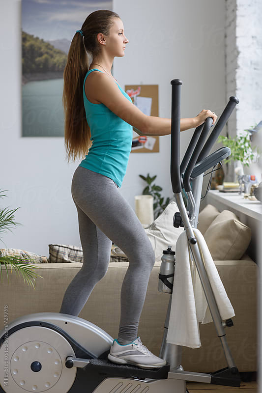 Woman running on elliptical trainer by Milles Studio for Stocksy United