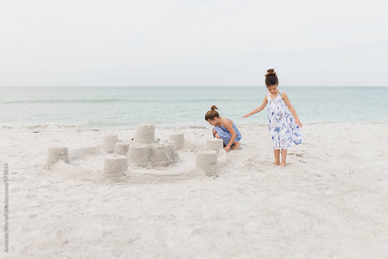 Two young girls building a sand castle by Amanda Worrall for Stocksy United