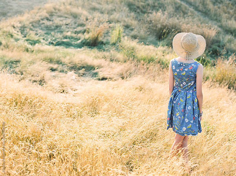 Rear view of a girl in a field, wearing a hat at sunset by Kirstin Mckee for Stocksy United