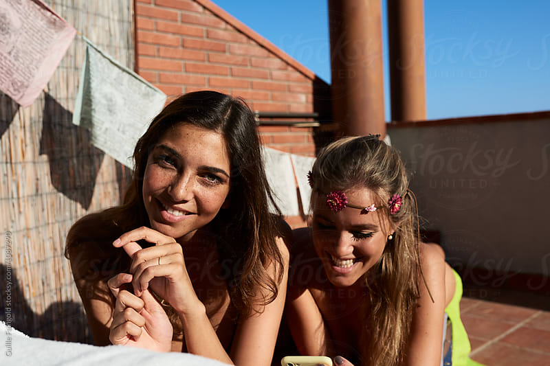Smiling girlfriends on deckchair on roof by Guille Faingold for Stocksy United