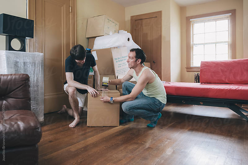 Gay Male Couple Packing and Unpacking Boxes Moving by Joselito Briones for Stocksy United
