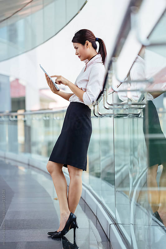 Attractive businesswoman working with her digital tablet by michela ravasio for Stocksy United