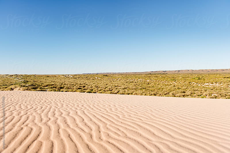 Wind blow ripples in sand dunes against the backdrop of the Cape Range National Park by Angela Lumsden for Stocksy United