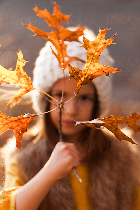 Pretty young girl holding a small branch with autumn leaves in front of her face by Amanda Worrall for Stocksy United