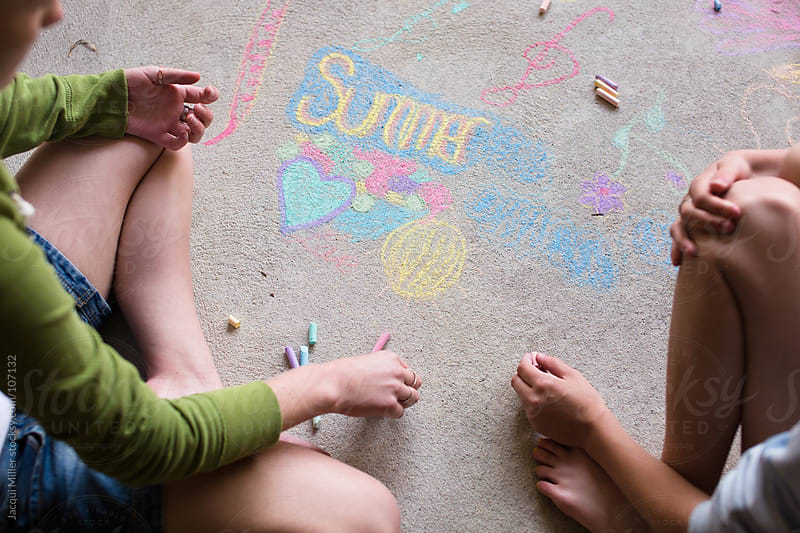 Two girls draw with chalk on a concrete floor by Jacqui Miller for Stocksy United