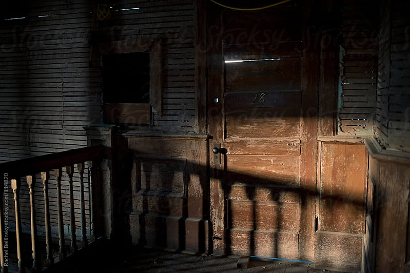 An old, splintered door in afternoon shadows at an abandoned school by Rachel Bellinsky for Stocksy United