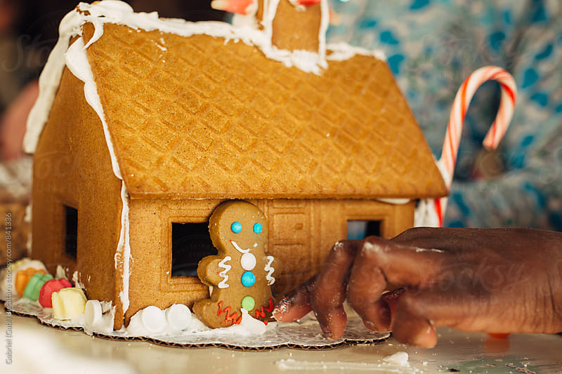 Black girl's hand working on a gingerbread house by Gabriel (Gabi) Bucataru for Stocksy United