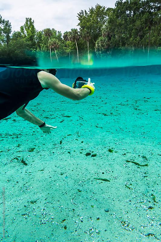 A snorkeler using a smartphone camera underwater by Adam Nixon for Stocksy United