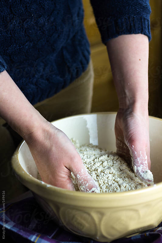 Woman mixing flour to make bread by Kirsty Begg for Stocksy United