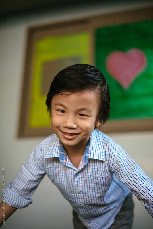 Portrait of a cute, little, handsome boy smiling at the camera by Lawrence del Mundo for Stocksy United