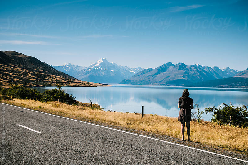 Rear view of woman tourist looking towards Aorkai / Mt Cook, New Zealand's highest peak.  by Thomas Pickard for Stocksy United