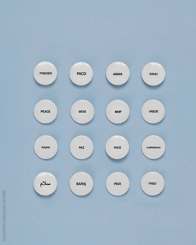 16 pins spelling the word PEACE in different languages by Laura Stolfi for Stocksy United