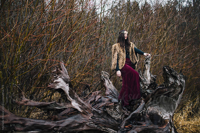 Girl standing on giant tree stump by Michelle Moore for Stocksy United