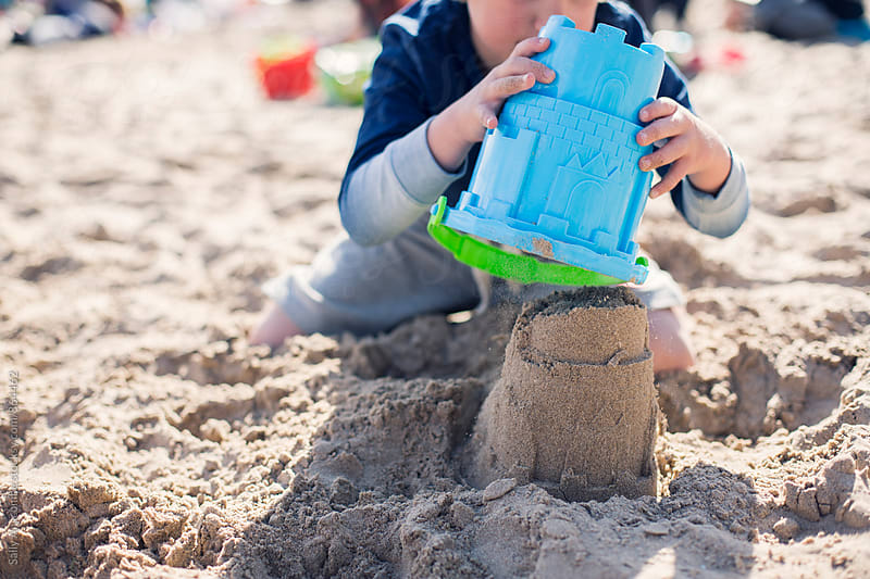 Child building a sandcastle  by sally anscombe for Stocksy United