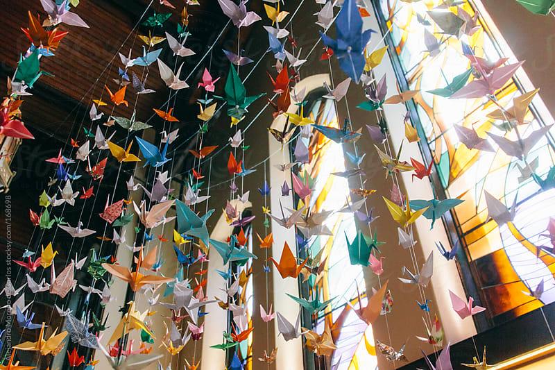 Colorful origami cranes suspended. Paper folding craft by Alejandro Moreno de Carlos for Stocksy United