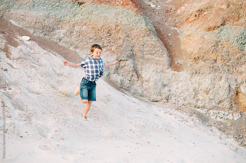 Boy runs down a sand dune with colorful rocks in background by Rebecca Spencer for Stocksy United