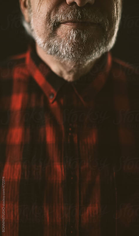 Cropped view of the grey beard of an old man on black background by BONNINSTUDIO for Stocksy United