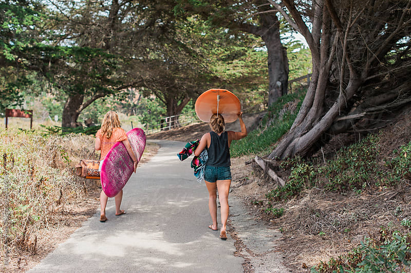 Two Women Carrying Surfboards Along a Path by Briana Morrison for Stocksy United