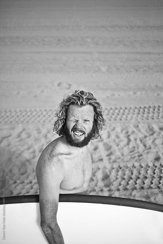 Young ginger man with beard standing on the beach looking into the sun by Denni Van Huis for Stocksy United