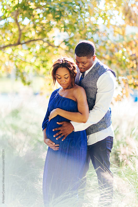 Pregnant woman and husband embracing in nature by Kristen Curette Hines for Stocksy United