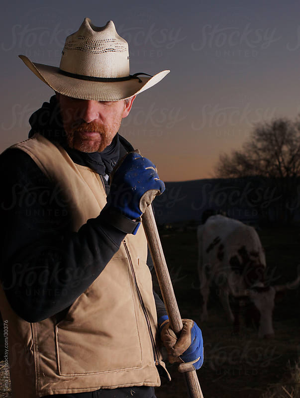 Cowboy leaning on pitfork after feeding cows at dusk.  by Tana Teel for Stocksy United